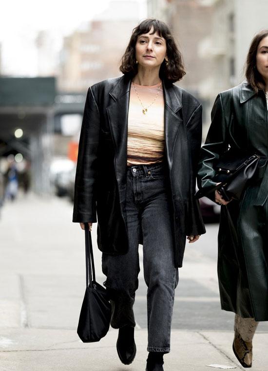 Девушка в серых прямых джинсах, топ и кожаный блейзер оверсайз