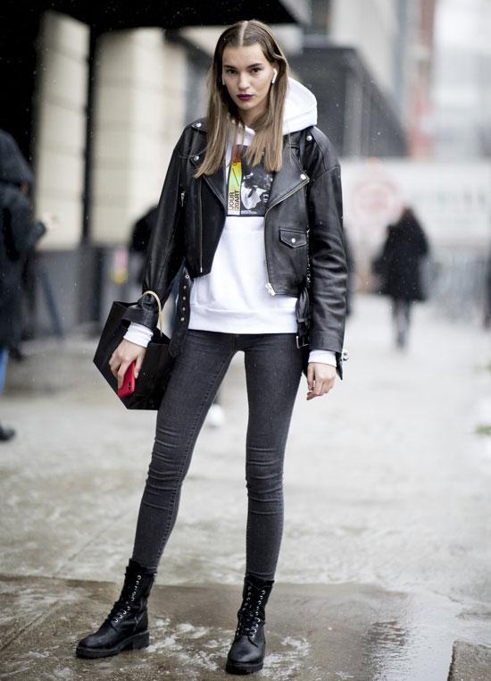 Девушка в серых скинни, белая худи, ботинки на шнуровке и куртка косуха
