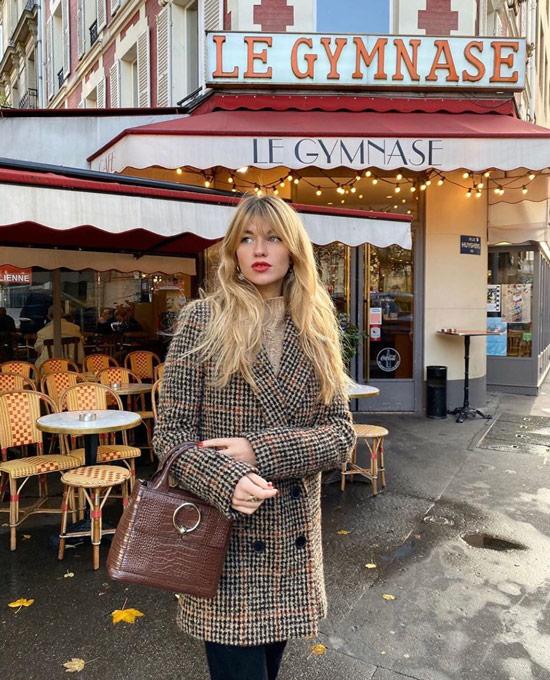 Девушка в шерстяном пальто в клетку, джинсы и коричневая сумочка
