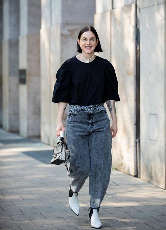 Девушка в широких серых джинсах, черная блузка и белые ботильоны