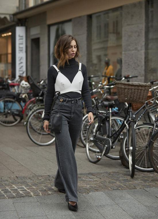 Девушка в широких серых джинсах. черная водолазка и туфли