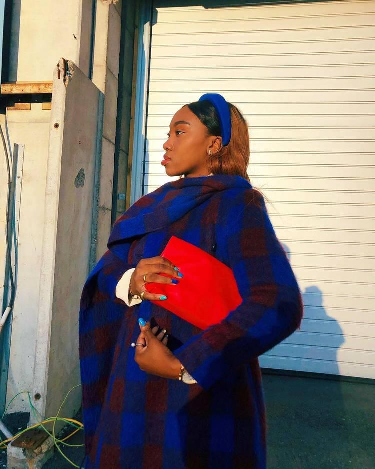 Девушка в синем пальто оверсайз в клетку, красный клатч и бархатный ободок