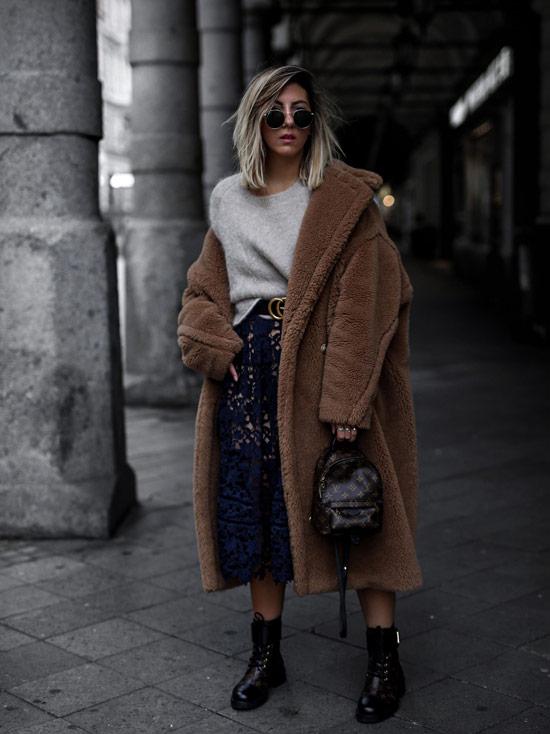 Девушка в синей юбке миди, серый свитер с ремнем и плюшевое пальто и черные ботинки