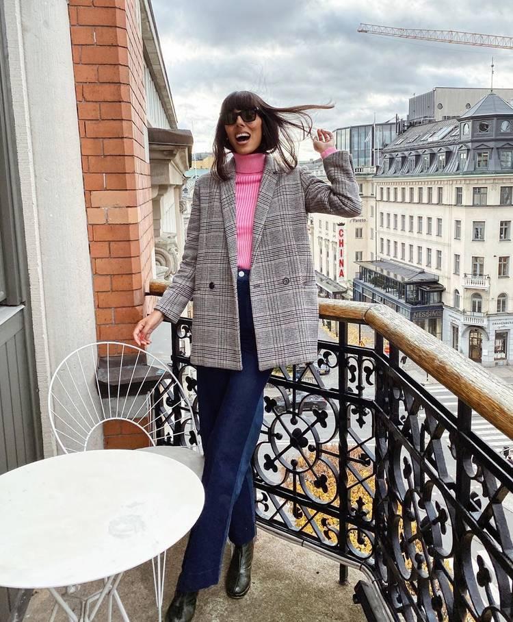 Девушка в синих джинсах клеш, розовая водолазка и серый пиджак в клетку