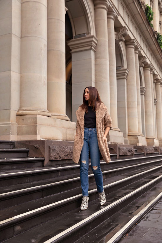Девушка в синих рванных джинсах, черный топ и бежевое пальто тедди