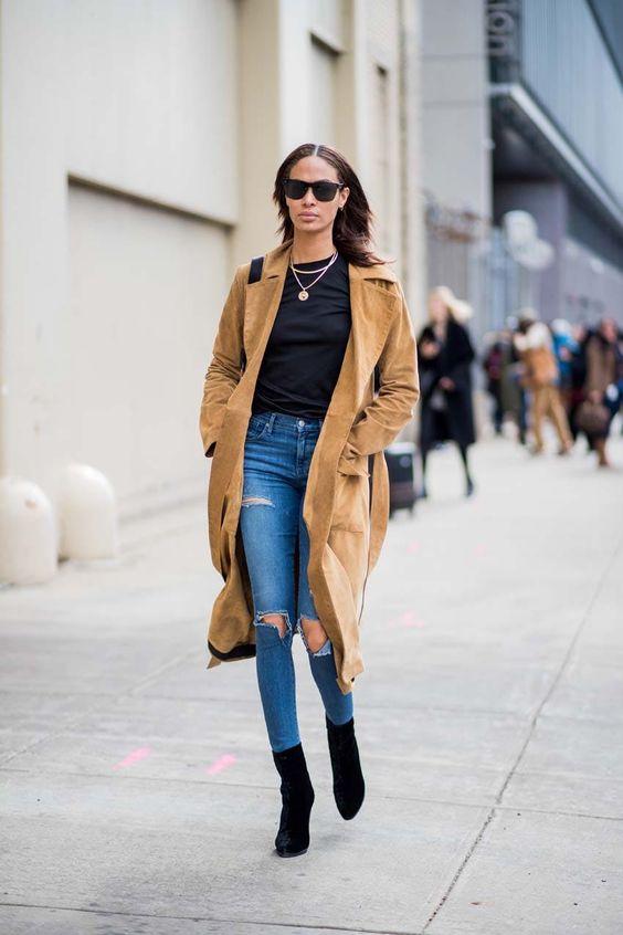 Девушка в синих рванных джинсах, черный топ и ботильоны, бежевое пальто