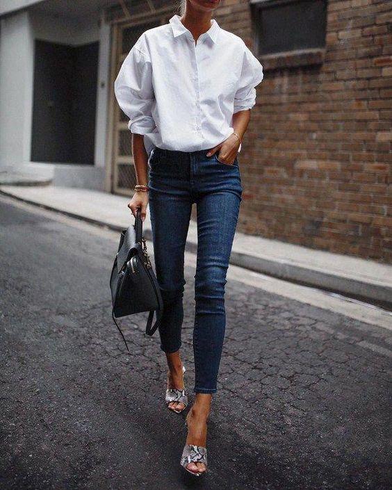 Девушка в синих узких джинсах, белая рубашка и сумка