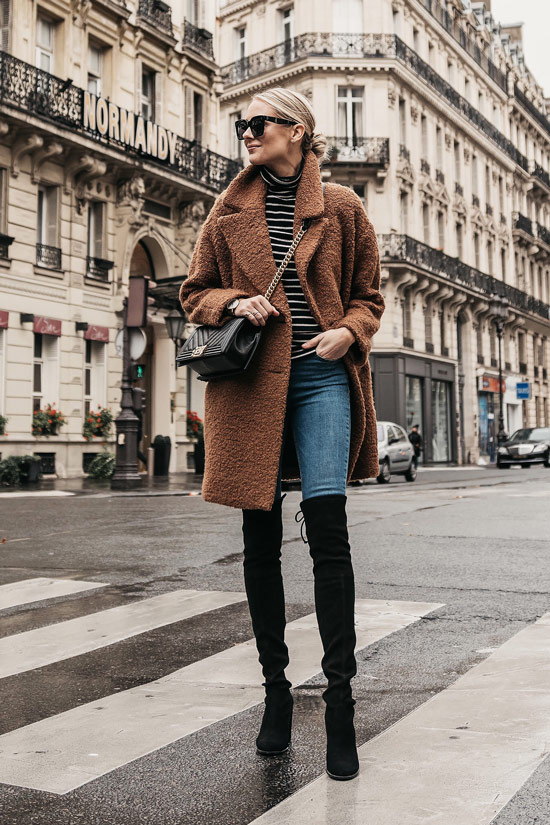 Девушка в синих узких джинсах, водолазка в полоску, коричневое пальто тедди и черные ботфорты
