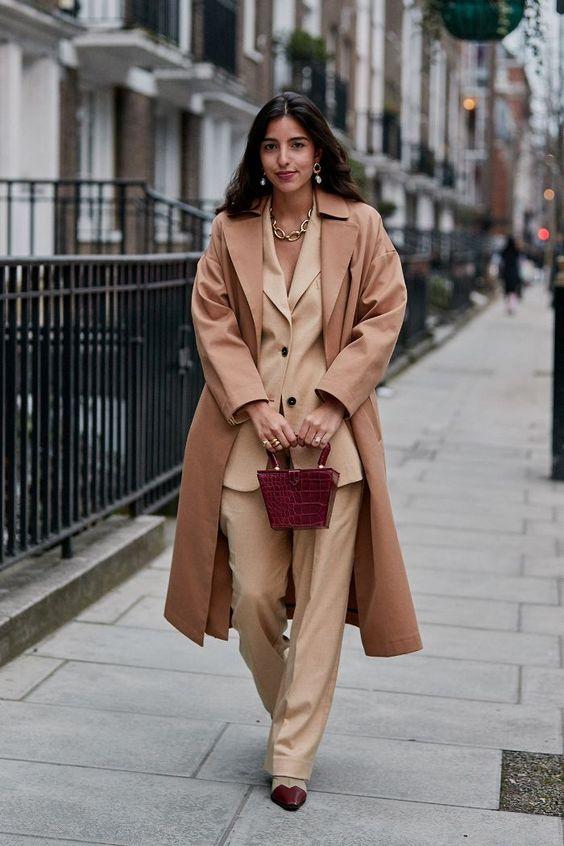 Девушка в светло-бежевом деловой костюме и плаще, бордовая сумочка