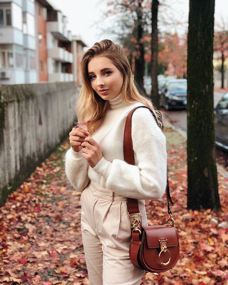 Девушка в светлых брюках, белый свитер и коричневая сумка