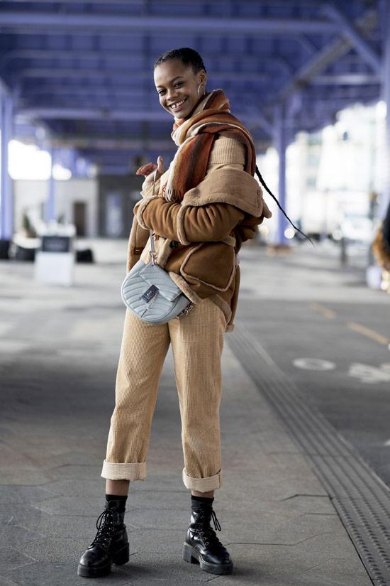 Девушка в светлых брюках, бежевый шарф и куртка, военные ботинки