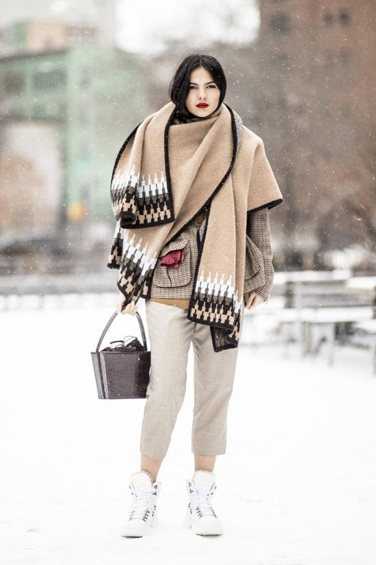 Девушка в светлых штанах, большой шарф и белые кроссовки