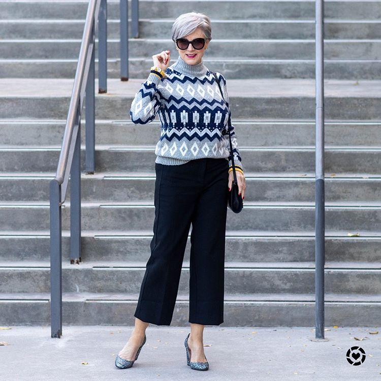Девушка в укороченных брюках, свитер с узорами и серые туфли