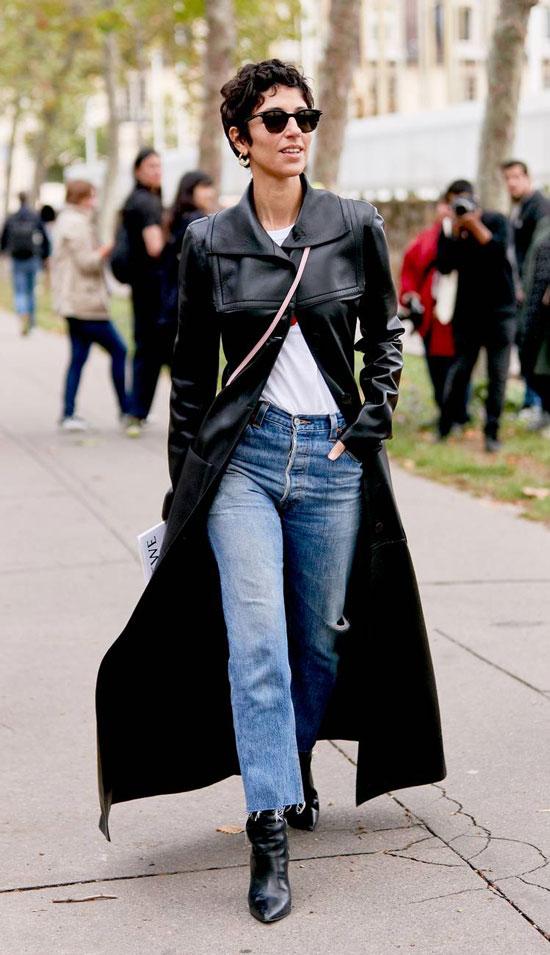 Девушка в укороченных джинсах, белая футболка и длинный кожаный плащ