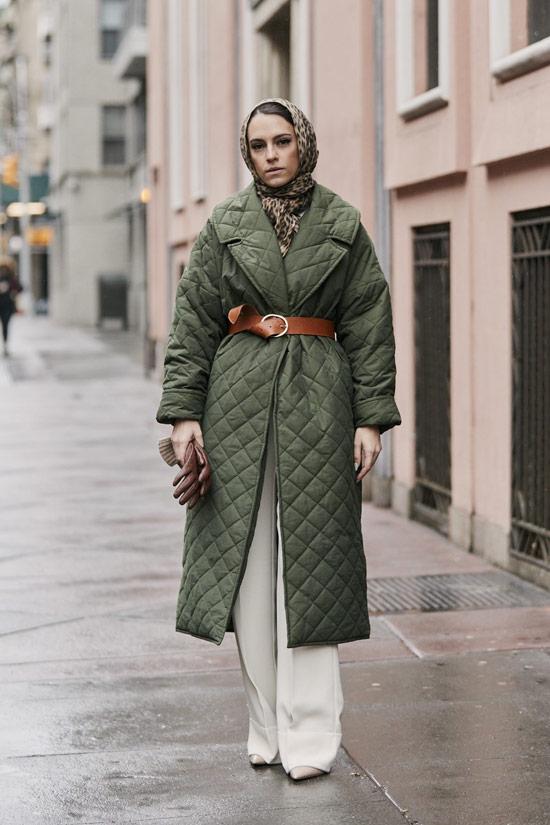 Девушка в зеленом пальто с ремнем, белые широкие брюки и сапоги