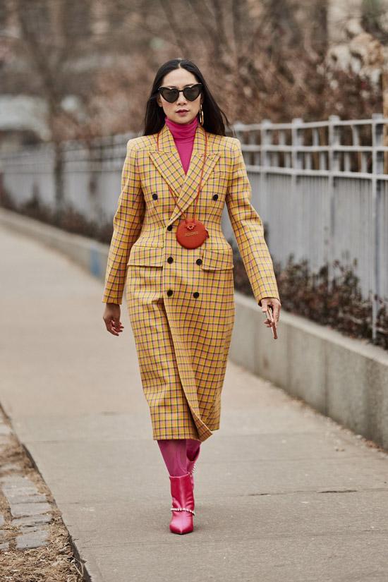 Девушка в желтом пальто в клетку, розовая водолазка и ботильоны