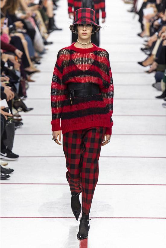 Модель в брюках в клетку, красно-черный свитер и черные туфли