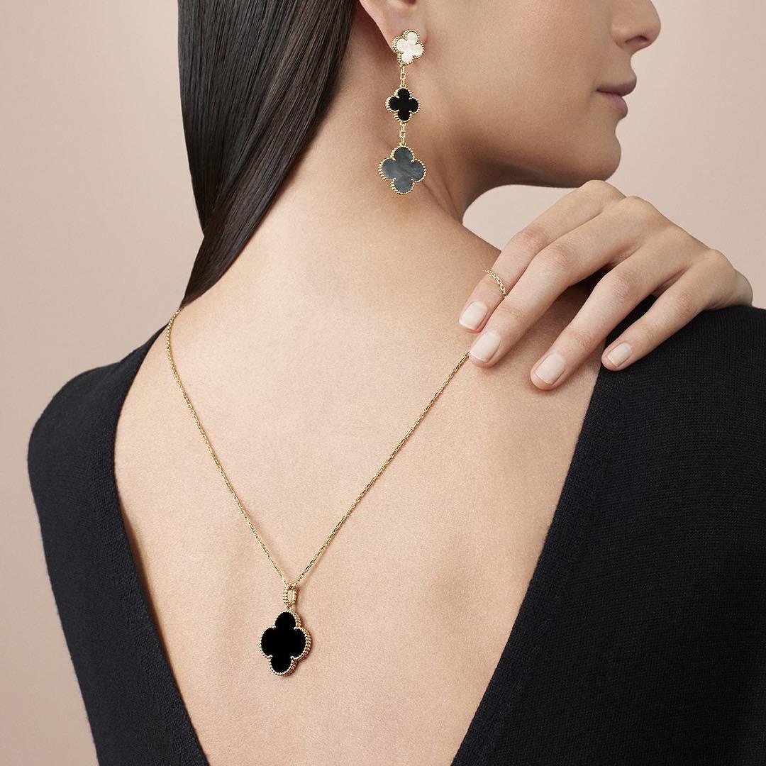 Модель в черном платье и золотая цепочка с подвеской