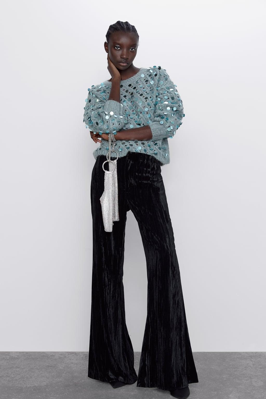 Модель в черных брюках клеш и серый свитер