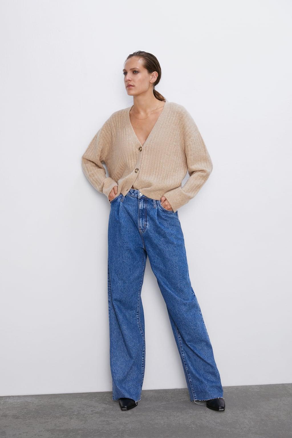 Модель в широких синих джинсах и бежевом кардигане