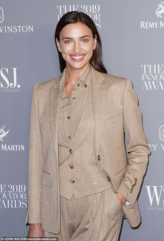 Ирина Шейк в бежевом брючном костюме и рубашке улыбается