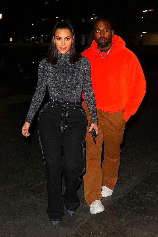 Ким Кардашьян в черных джинсах и Канье Уэст в оранжевой толстовке