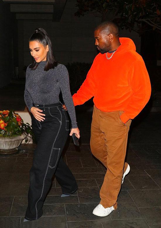 Ким Кардашьян в черных джинсах с белыми швами и серой водолазке