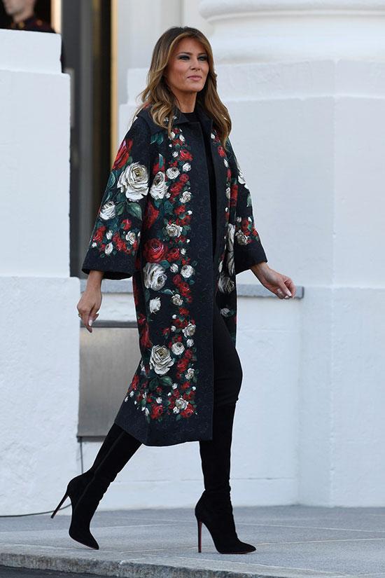 Мелания Трамп в черных брюках, сапогах и цветочном пальто