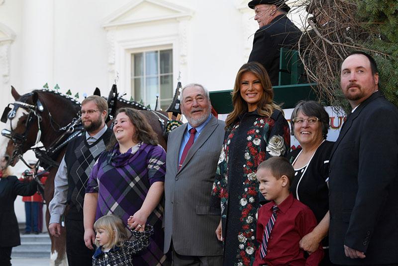 Мелания Трамп в цветочном пальто на совместном фото возле телеги с рождественской елкой