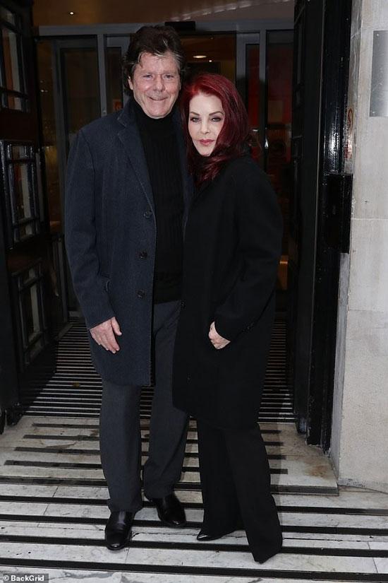 Присцилла Пресли в черном пальто, туфлях и брюках клеш