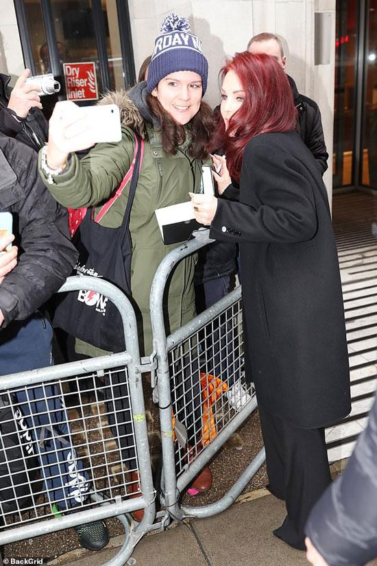 Присцилла Пресли в черном пальто делает селфи с фанатами
