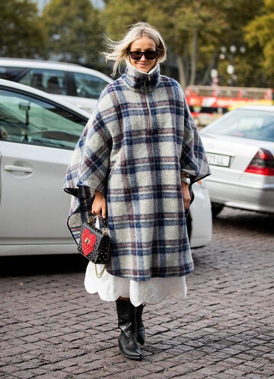 Девуша в объемном пальто в клетку и ковбойсие сапоги