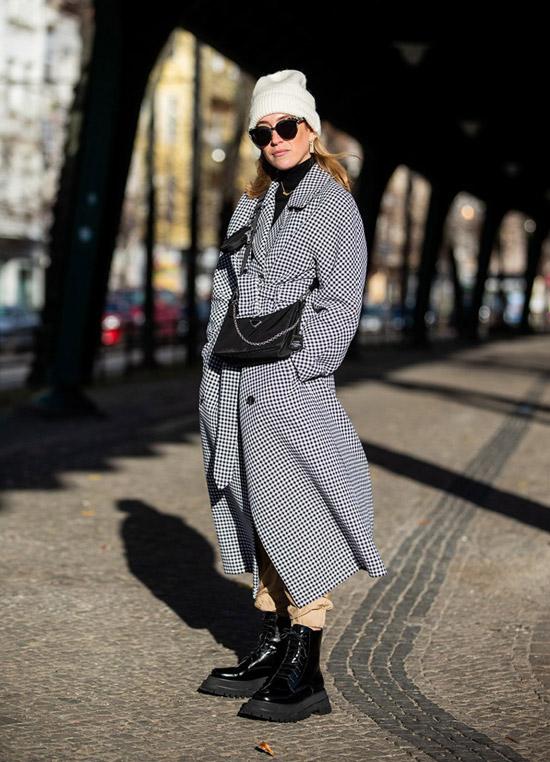 Девушка в сером пальто в клетку и грубые черные ботинки