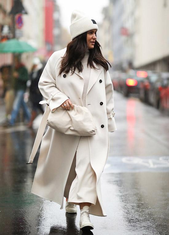 Девушка в белом длинном пальто, кроссовки и мягкая сумка