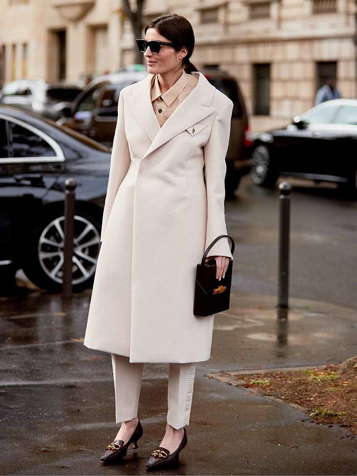 Девушка в белом пальто, брюки и туфли на невысоком каблуке