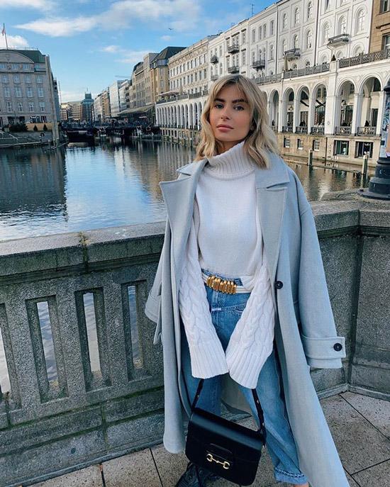 Девушка в белом свитере, джинсы с ремнем и голубое пальто