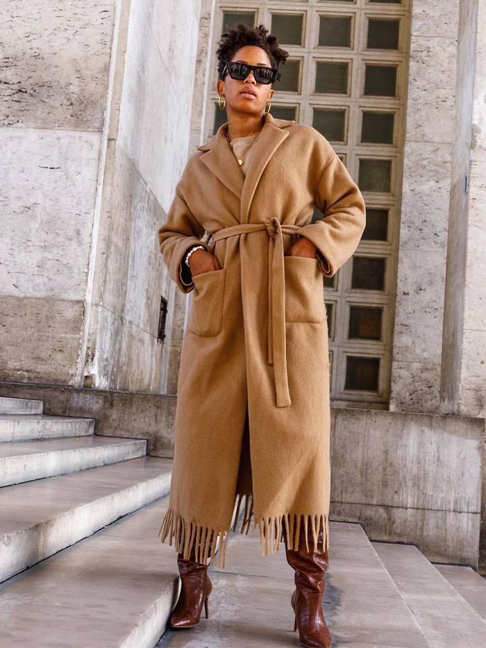 Девушка в бежевом пальто с поясом и коричневые сапоги
