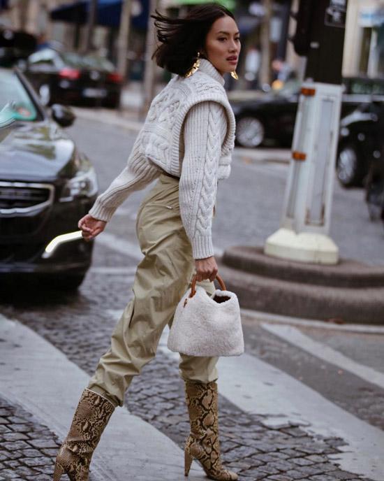 Девушка в бежевых брюках, бежевый свитер и сапоги со змеиным принтом
