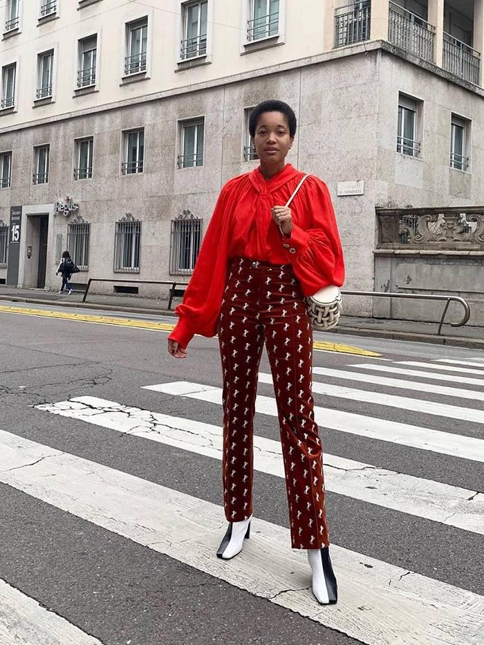 Девушка в бордовых брюках с высокой талией, красная блузка и ботильоны