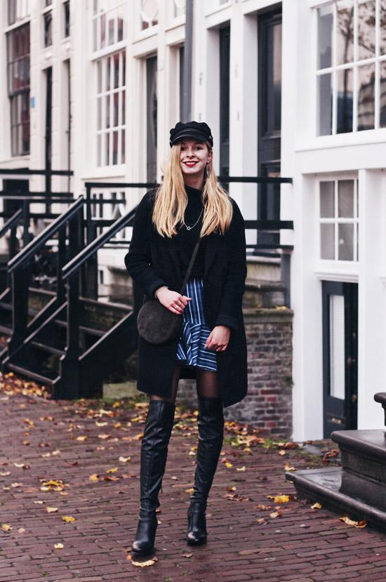 Девушка в черных ботфортах, черное пальто и мини юбка в полоску