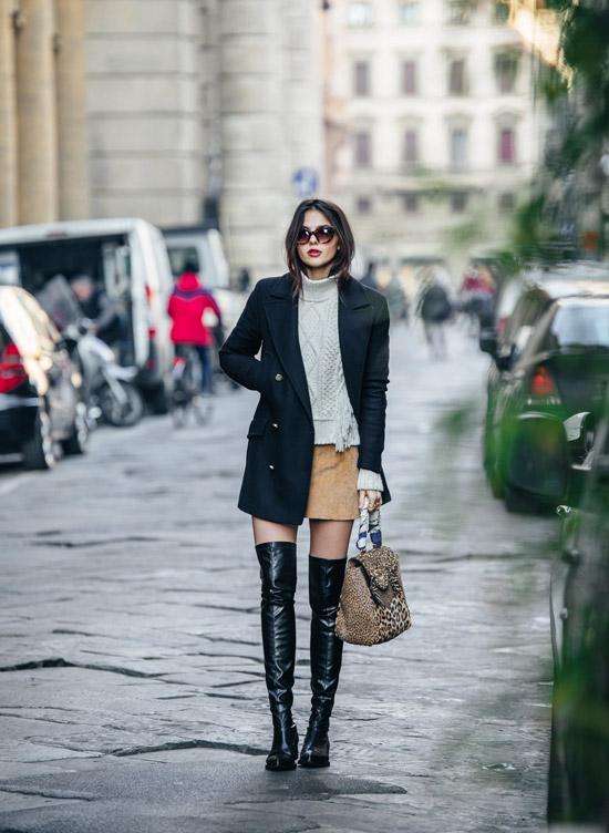 Девушка в черных ботфортах, мини юбка, серый свитер и черное пальто