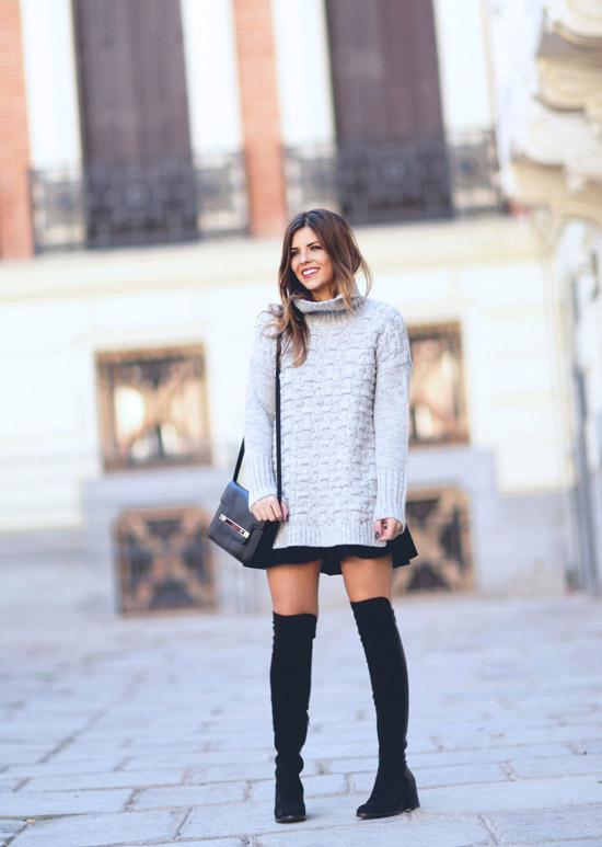 Девушка в черных ботфортах, серый свитер оверсайз и мини юбка
