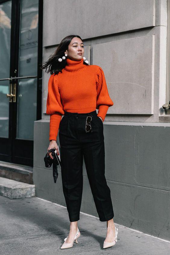 Девушка в черных брюках, оранжевый свитер и туфли