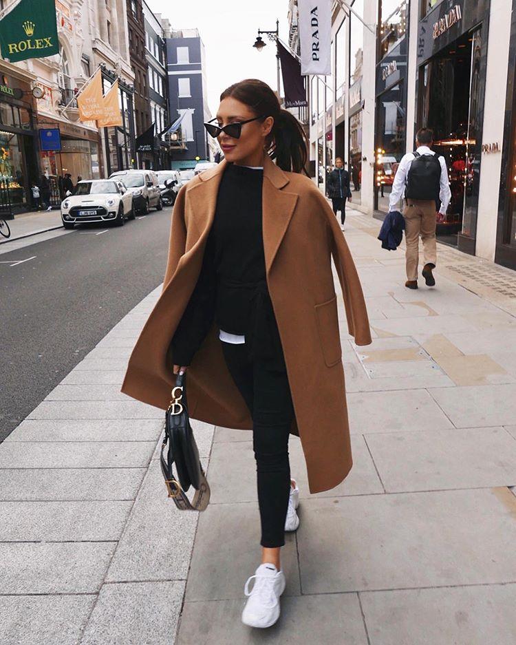 Девушка в черных джинсах, кроссовки и коричневое пальто