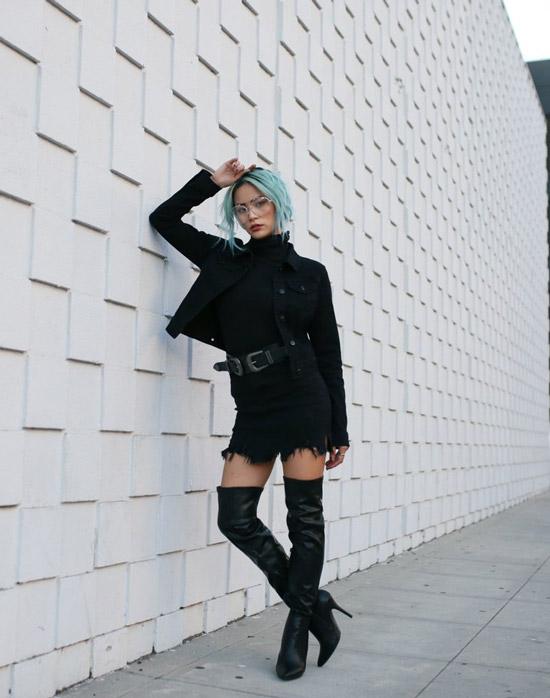 Девушка в черных кожаных ботфортах на каблуке, мини юбка с ремнем и черная водолазка