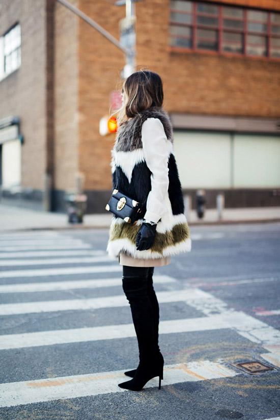 Девушка в черных замшевых ботфортах, меховая жилетка и квадратная сумочка