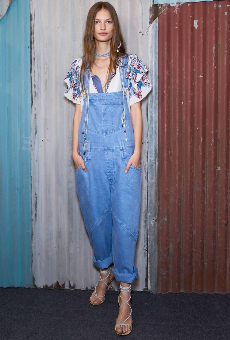 Девушка в голубом джинсовом комбинезоне, блузка и босоножки на на тонких ремешках