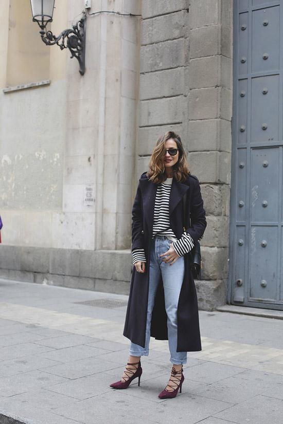 Девушка в голубых джинсах, пуловер в полоску и длинное пальто