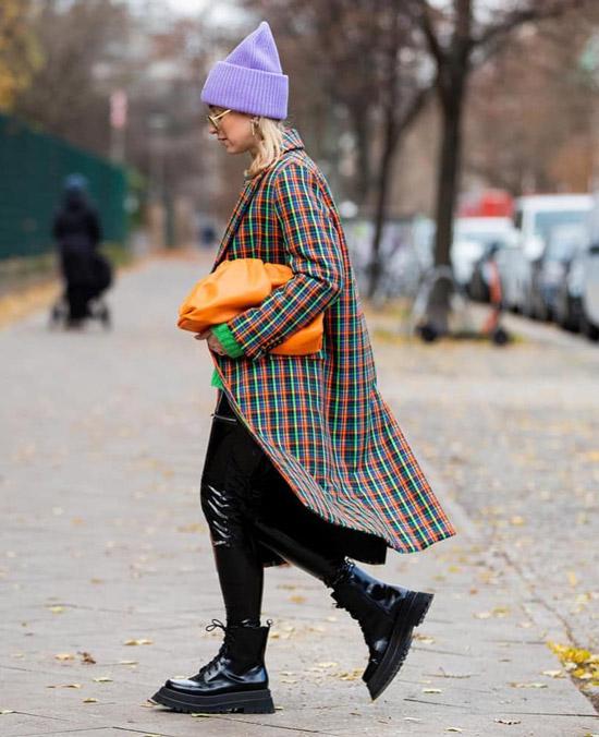 Девушка в лакированных леггинсах, пальто в клетку, черные ботинки и мягкий клатч