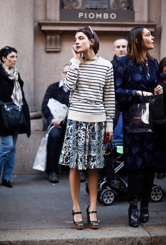 Девушка в миди юбке с принтом и светлый свитер в полоску, черные туфли